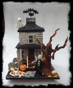 "Halloween Haunted House - This creation was made for a Halloween party.  It is based on a cake by ""Tickle Your Fancy Cakes"".  The House is cake covered in MMF, with MMF and candy melt details.  The ghost is a cakepop with a MMF drape. Tree is a PVC pipe and food grade wires wrapped in choc fondant."