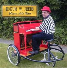 Piano Professor Hokum W. Jeebs plays and rides a three wheeled cart.