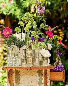 Garrafas e vidros de diferentes origens entram na composição de Claudia Regina, da La Calle Florida. As flores usadas são igualmente variadas: lisianto, maria-sem-vergonha, gérbera, campânula e goivo