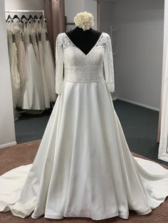 A beautiful ballgown style with a v neckline, illusion lace shoulder detail, illusion lace three quarter length sleeves, finished with a illusion lace v back and full satin skirt. Zip back and buttons. Discount Designer Wedding Dresses, Satin Skirt, Dream Wedding Dresses, Bridal Boutique, Illusion, Townhouse, One Shoulder Wedding Dress, Ball Gowns, Neckline