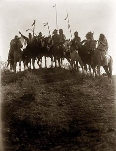 a dramatic photograph of a Crow War Party. It was made in 1908 in Montana by Edward S. Curtis.  The photo illustrates Eight Crow Indians on horseback, silhouetted on the top of a hill. The man that is second from the left is pointing off into the distance.