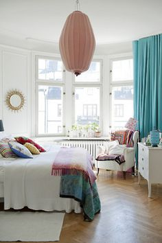 I love the unique light fixture and the turquoise curtains. There is something that draws me to a mostly white room with bright accents. Not sure I would like living in an all white room though???