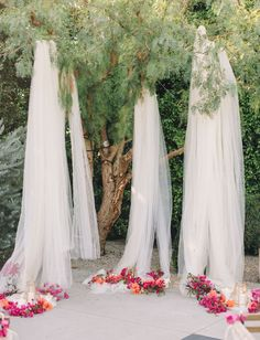 Hang tulle from the trees for an outdoor wedding backdrop.