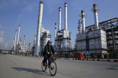 In this Monday, Dec. 2014 photo, an Iranian oil worker rides his bicycle at the Tehran& oil refinery south of the capital Tehran, Iran. World Bank Report, Oil Refinery, Nuclear Deal, Nuclear Energy, The Washington Post, Oil And Gas, Cn Tower, Street View, China