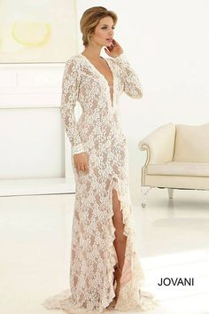 Beautiful long sleeve lace bridal gown features a plunging neckline and open back