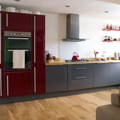 Red and grey modern kitchen - butcher block and wooden floor warms it up!