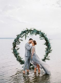 11 More Giant Wedding Wreaths: The Hottest Wedding Trend: #9. Evergreen wreath backdrop right in the sea for a coastal ceremony