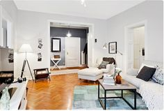 Dark grey painted walls of entry lead into the white and bright living room with light grey painted walls