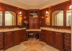 Craftsman bathroom with rich wood vanities, large mirrors and makeup sitting area