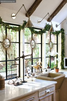 Jill Sharp's kitchen during Christmas holidays.  Kasler's popular sunburst mirror set, hung from lush garland, adds warmth and architectural interest to the bank of steel and glass windows in the kitchen.