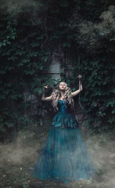 Girl wearing a blue gown outside surround by ivy: