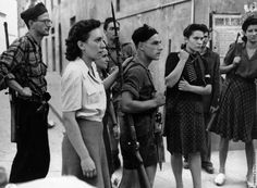 Italian anti-fascist partisans regroup in the Valley of Aosta above the Colle del Piccolo San Bernardo pass in the Italian Alps. Italy. 1945. Note the strong presence of female fighters in the group.