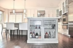 """Who says you can't have a glitzy bar in your kitchen? Here, the end of an island is transformed into that cabinet (and we kind love that background that screams """"party"""" too). See more at DC Renos »"""