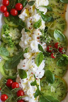 beautiful dish of tomatoes with buffalo mozzarella and garden herbs and flowers