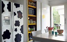 Por pura diversão, a arquiteta Fabiana Frattini cobriu a geladeira com adesivos de estampa de pele de vaca e pintou de amarelo o interior dos armários da cozinha