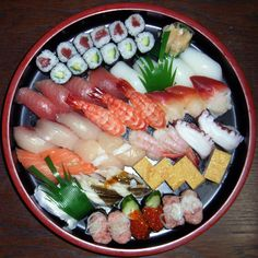 Sushi - National dish of Japan. Cooked vinegared rice with seafood or vegetables served with pickled ginger, wasabi and soy sauce.