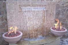 Ethereal combination of fire bowls, stone, and water sheeting down is just amazing. Design by Unique Landscapes by Griffin of Arizona.