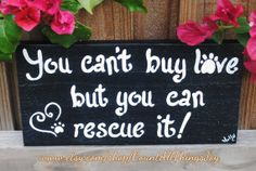 """You can't buy love but you can rescue it"" rustic wooden sign made from fence slat. The sign is 11"" x 5-""x1/2"", painted in the color of your choice, distressed if desired. The paw print can be replaced with a horse hoof, bird print, etc. Signed."