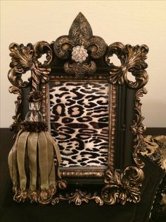 Black and gold ornate frame with a tassel and crystals