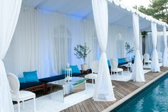 For a recent pool party, the team at Swank Productions kept the decor streamlined, with a mostly white color palette, mirrored furnishings, and plenty of sheer draping.