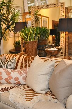 Neutral sofas covered with animal fur, plants and paired lamps on the backdrop of neutral walls.