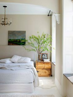 Beige wall paint and white floors lend this bedroom a naturally minimalist vibe.