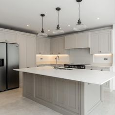 This stunning kitchen renovation features light grey, handmade beaded cabinets with a large island taking centre stage. With seamless white worktops and traditional pendant lighting, this kitchen has timeless appeal #handmadekitchen #greykitchen #kitchenisland