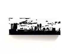 Jacksonville Skyline Canvas Wall Art (White with Black, 12 x 4 inches). Jacksonville Skyline Canvas Wall Art Can be easily hung on the wall or stood alone on a surface! White Paint with Black Ink. (1) 12 x 4 inch archival & acid-free stretched cotton canvas. © Ink the Print All prints dated and signed on back. *All artwork is painted & printed by hand, resulting in possible minor differences from the photos. This makes each piece unique.
