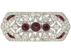 This sparkling Art Deco diamond brooch is accented by three center round cut garnets and calibre cut garnets at the corners. The old cut diamonds are in millegrain settings in a geometric openwork design.