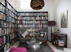 The back half of the living room houses an impressive library. The MDF bookcases were made by a builder and painted. Quirky accents include a Zebo rug from Alternative Flooring.