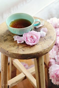 Teacup with flower and some petals on stool - homely shot