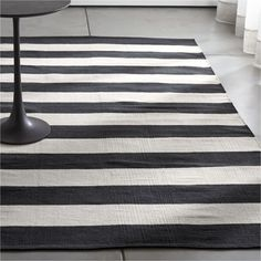 Shop Olin Black Striped Cotton Dhurrie Rug.  Broad bands of black and ivory stretch horizontally across this modern and sophisticated cotton rug hand-loomed by artisans skilled in flat-weave construction.  Stripes scale up with the rug size.