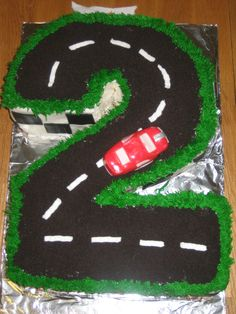 2 Year Old's Car Cake - I made this cake for my 2 year old little boy. Iced in buttercream w/ fondant car, crushed oreos for road chocolate rocks for bottom border.
