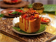 Mutton Bunny Chow - A fresh loaf, hollowed out and filled with fragrant curry. An iconic South African dish. Jamaican Recipes, Spicy Recipes, Indian Food Recipes, Ethnic Recipes, South African Dishes, South African Recipes, Salted Caramel Chocolate Tart, Chocolate Tarts, Salted Caramels
