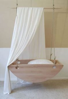 A beautiful bassinet. Handcrafted from wood and suspended from the ceiling.