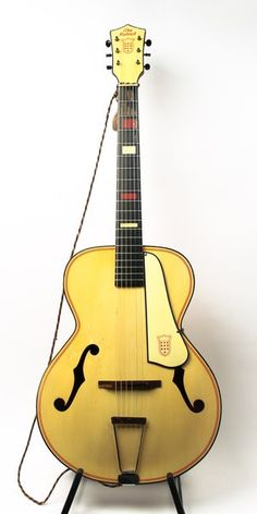 "A relic from the war bonds days, a rare solid maple Kay archtop with patriotic appointments. Blue paint binding on top, headstock, and pickguard, with U.S. shield adorned on pickguard and headstock. 15.5"" lower bout, 11"" upper bout. There is a bow in the neck, so the action is high, but would make a great slide guitar."
