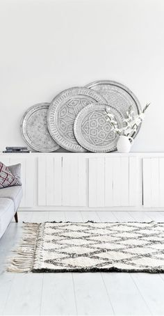 = white board sideboard, stacked Moroccan plates and rug by El Ramla Hamra