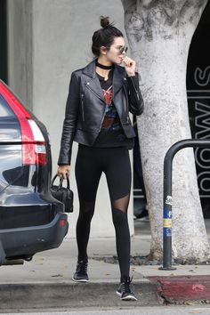 Kendall Jenner wearing black leather jacket, black leggings, and black rock tshirt, black choker, black handbag, and sneakers (Fashion Edgy Fans)