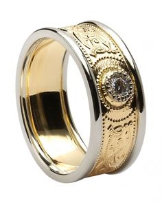 An impressive two-tone men's Celtic Ring and Irish wedding band is centered with a diamond and accented in ancient symbols known as the Warrior Shield. Diamond: G color, VS clarity, 0.10 cts. Ring width: 0.28 inches. Sizes 9-13 (including half sizes). This ring is made to order. Please allow approximately 10-14 working days for this item to be completed. Made in Ireland by Boru and hallmarked by the Assay Office in Dublin Castle.