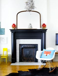 High gloss black fireplace with white tile and HUGE trim...also eames + fox pillow AND vintage yellow chair