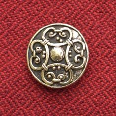 Viking Round Brooch, 10th century, Birka, Uppland, Sweden. 900-1000AD Small circular bronze brooch used by women to fasten the neck of their linen underdress. Classified as Jansson's Group 4B of cast brooches, decoration of four volutes and pseudogranules, imitating filigree work. Found at Birka in grave 762...A small loop on the rear is for hanging utensils or ornaments. Dia 2.7 cm Bronze or brass, iron pin