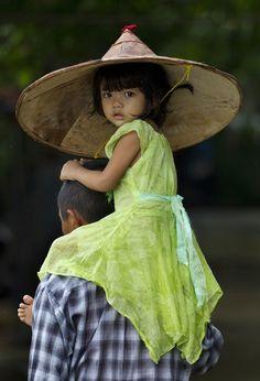 "fotojournalismus: "" A child is carried by an adult in Khanaung Chaung Wa village, southeast of Yangon, Myanmar on June [Credit : Gemunu Amarasinghe/AP] """