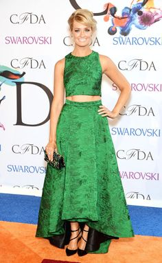 Beth Behrs shows off just a sliver of skin in a bright green crop top and full-skirt ensemble.