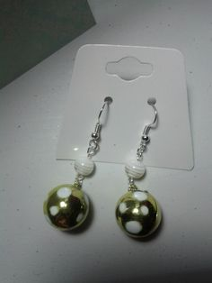 These adorable earrings are handmade by me. They each feature a round green bead with white spots and a coordinating white striped round bead. $6