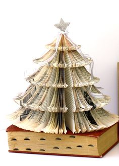 Old Book Christmas Tree. Made from an old book titled Music in Europe and the United States, it's topped with a silver glitter covered star, and white organza with silver cascading bows. The page edges have been stained with a brown paint wash.