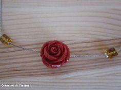 Dettaglio collana con pietre dure gialle e rosa in resina rossa
