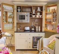 Here is the ultimate small kitchen with a refrigerator, electric smooth top burner, microwave and dish and food storage all behind the doors of a freestanding hutch. This would be ideal for a small guest house or cabin.