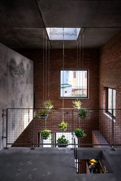 As well as on the roof, planting continues through the house, with a combined sink and planter made from concrete holding an indoor tree, and a selection of green plants suspended from the ceiling. Water Collection System, Style Tropical, Indoor Trees, Agricultural Land, Construction Process, Loft, Large Windows, Skylight, Brick Wall