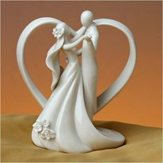 """WeddingDepot.com ~ Wedding Cake Topper - Everlasting Love ~ The bride and groom share a romantic embrace in front of an open scrolling heart. Porcelain flowers accent the bride's veil and the edge of her dress. Made of glazed porcelain this cake topper can serve as a beautiful keepsake figurine for years to come. Measures 5.25"""" wide x 6.5"""" tall."""