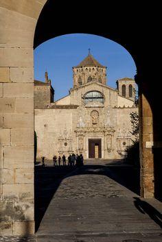 A través de l'arc de la Porta Daurada es pot veure l'entrada barroca de l'església al fons Monestir de Poblet.   Catalonia